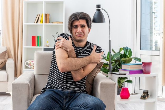 Jonge man in vrijetijdskleding die er bezorgd en verward uitziet terwijl hij op de stoel zit in een lichte woonkamer