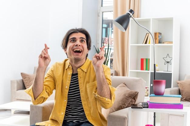Jonge man in vrijetijdskleding die er blij en opgewonden uitziet en wensen doet terwijl hij zijn vingers kruist terwijl hij op de stoel zit in een lichte woonkamer