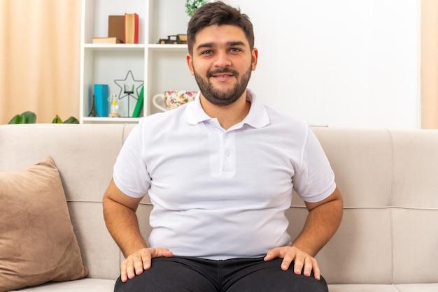 Jonge man in vrijetijdskleding die er gelukkig en positief uitziet en een weekend thuis doorbrengt, zittend op een bank in een lichte woonkamer living