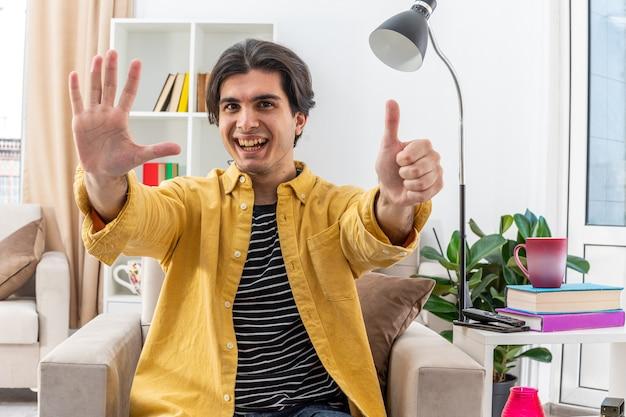 Jonge man in vrijetijdskleding die er gelukkig en vrolijk uitziet en nummer zes toont met vingers op de stoel in een lichte woonkamer