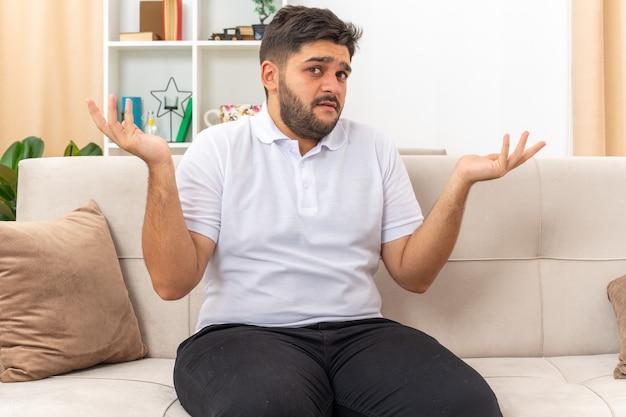 Jonge man in vrijetijdskleding die er verward uitziet en zijn armen naar de zijkanten spreidt, zittend op een bank in een lichte woonkamer