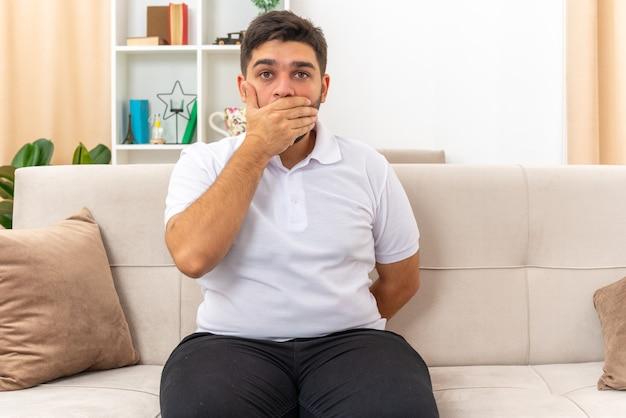 Jonge man in vrijetijdskleding die geschokt is en zijn mond bedekt met de hand zittend op een bank in een lichte woonkamer