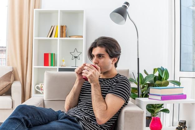 Jonge man in vrijetijdskleding die hete thee drinkt uit een mok zittend op de stoel in lichte woonkamer