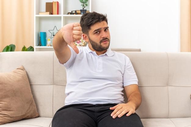 Jonge man in vrijetijdskleding die kijkt met een serieus gezicht met duimen naar beneden zittend op een bank in een lichte woonkamer