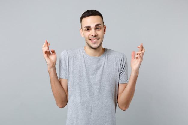 Jonge man in vrijetijdskleding die lippen bijt, wachtend op een speciaal moment, vingers gekruist houden, wensen doen making
