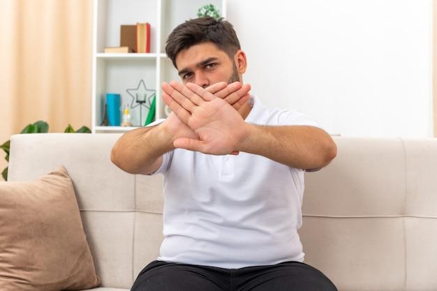 Jonge man in vrijetijdskleding die met een serieus fronsend gezicht kijkt en een stopgebaar maakt terwijl hij zijn armen kruist terwijl hij op een bank in een lichte woonkamer zit