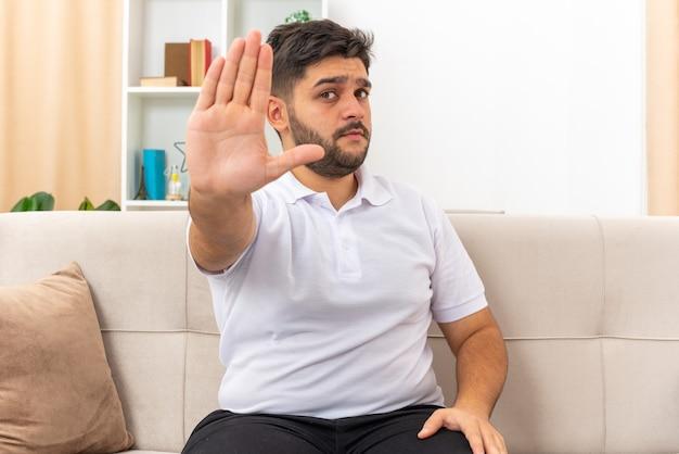Jonge man in vrijetijdskleding die met een serieus gezicht kijkt en een stopgebaar maakt met de hand zittend op een bank in een lichte woonkamer