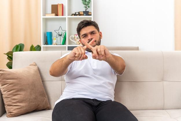 Jonge man in vrijetijdskleding die met een serieus gezicht kijkt en een verdedigingsgebaar maakt terwijl hij zijn vingers kruist terwijl hij op een bank in een lichte woonkamer zit