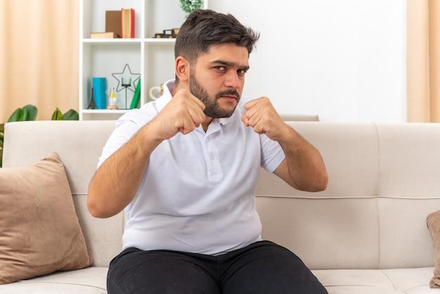 Jonge man in vrijetijdskleding die met gebalde vuisten kijkt als een winnaar die op een bank in een lichte woonkamer zit