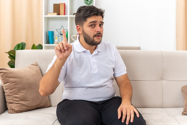 Jonge man in vrijetijdskleding die op zoek is naar een wijsvinger met een nieuw idee zittend op een bank in een lichte woonkamer