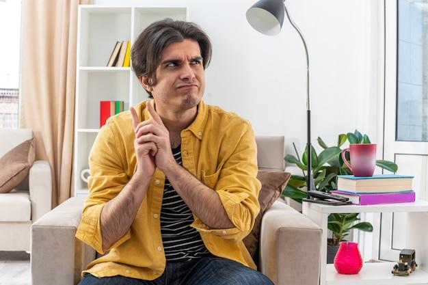 Jonge man in vrijetijdskleding die opzij kijkt met een peinzende uitdrukking, zittend op de stoel in een lichte woonkamer