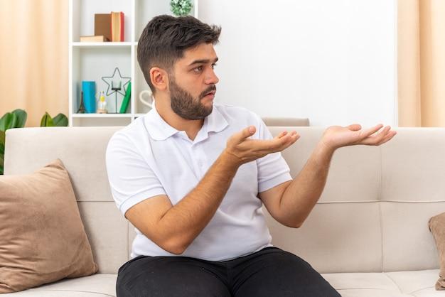 Jonge man in vrijetijdskleding die opzij kijkt verward presenteert met armen iets zittend op een bank in lichte woonkamer living