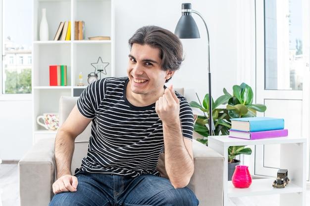 Jonge man in vrijetijdskleding die sluw lacht en geldgebaar maakt en vingers wrijft terwijl hij op de stoel zit in een lichte woonkamer