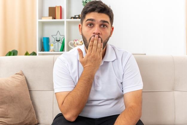 Jonge man in vrijetijdskleding die verbaasd en verrast kijkt en de mond bedekt met de hand zittend op een bank in een lichte woonkamer