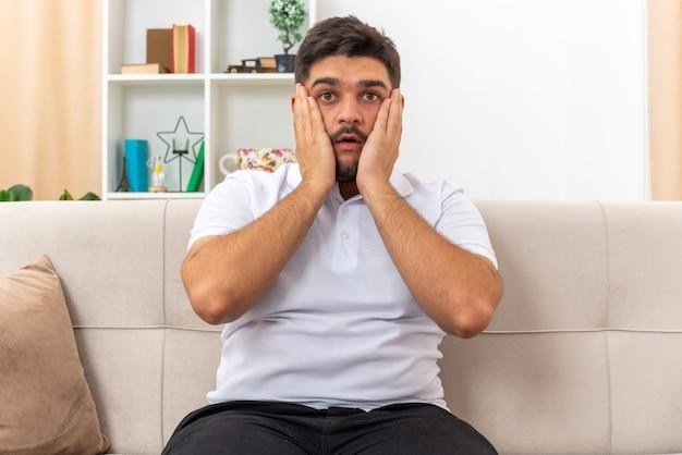Jonge man in vrijetijdskleding die verbaasd en verrast kijkt en een weekend thuis doorbrengt, zittend op een bank in een lichte woonkamer