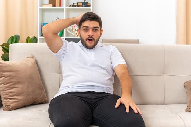 Jonge man in vrijetijdskleding die verbaasd en verrast kijkt met de hand op zijn hoofd zittend op een bank in een lichte woonkamer