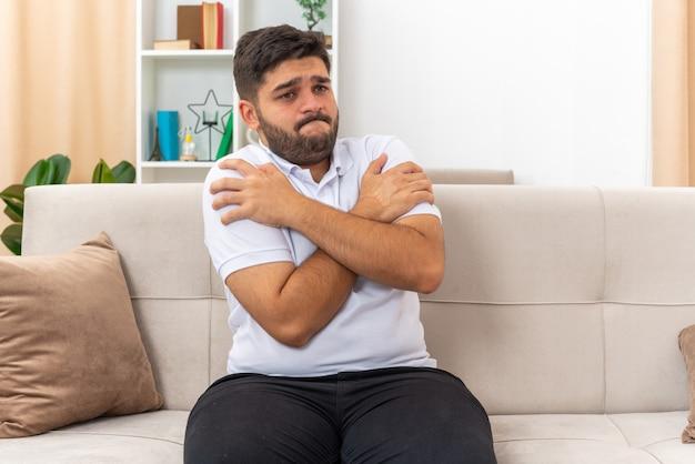 Jonge man in vrijetijdskleding die verward en bezorgd opzij kijkt met gekruiste armen op de borst zittend op een bank in een lichte woonkamer