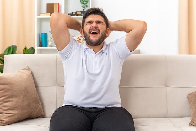 Jonge man in vrijetijdskleding die verward en gefrustreerd kijkt met handen op zijn hoofd zittend op een bank in lichte woonkamer living