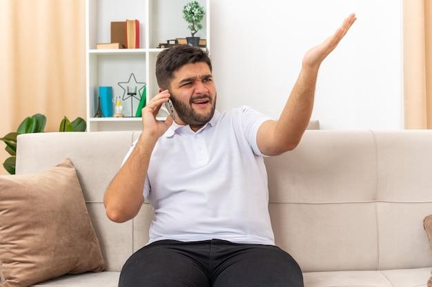 Jonge man in vrijetijdskleding die verward en ontevreden kijkt terwijl hij op een mobiele telefoon praat en zijn arm in verontwaardiging opheft, zittend op een bank in een lichte woonkamer