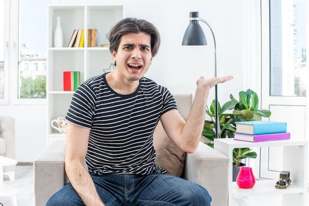 Jonge man in vrijetijdskleding die verward en ontevreden zijn arm opheft in ongenoegen en verontwaardiging zittend op de stoel in lichte woonkamer