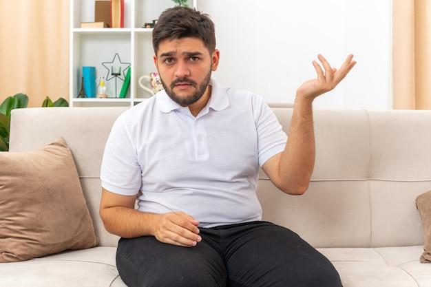 Jonge man in vrijetijdskleding die verward zijn arm opsteekt in ongenoegen en verontwaardiging zittend op een bank in lichte woonkamer