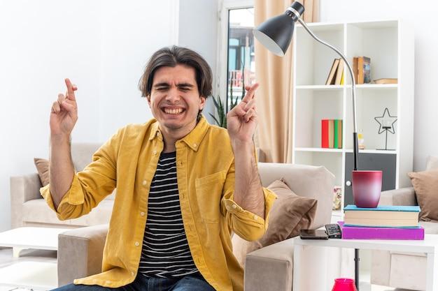 Jonge man in vrijetijdskleding die vingers kruist met gesloten ogen en wens doet met hoopsuitdrukking zittend op de stoel in lichte woonkamer