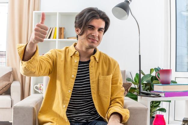 Jonge man in vrijetijdskleding die vrolijk lacht en duimen laat zien terwijl hij op de stoel zit in een lichte woonkamer