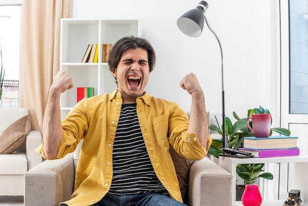 Jonge man in vrijetijdskleding, gek blij en opgewonden schreeuwend met gebalde vuisten zittend op de stoel in lichte woonkamer