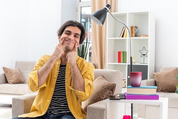 Jonge man in vrijetijdskleding glimlachend wijzend met wijsvingers naar zijn nepglimlach zittend op de stoel in lichte woonkamer