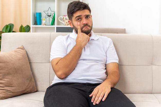Jonge man in vrijetijdskleding met droevige uitdrukking wijzend naar zijn oog zittend op een bank in lichte woonkamer