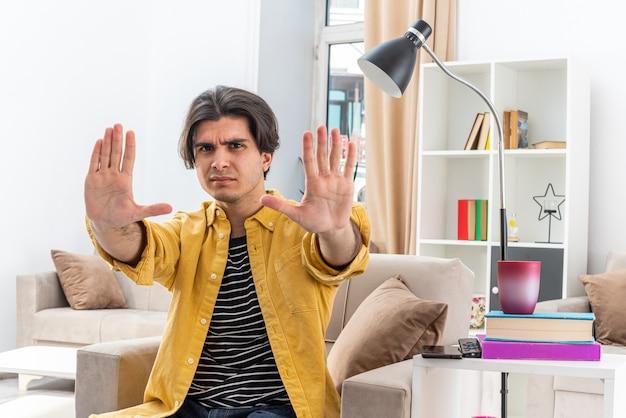 Jonge man in vrijetijdskleding met een ernstig gezicht, bezorgd om een stopgebaar te maken met handen zittend op de stoel in een lichte woonkamer