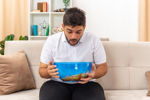 Jonge man in vrijetijdskleding met een kom chips die blij en verrast naar ze kijkt terwijl hij op een bank in een lichte woonkamer zit