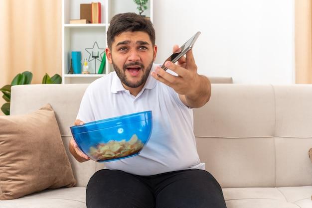Jonge man in vrijetijdskleding met een kom chips en een smartphone die er verward uitziet terwijl hij op een bank in een lichte woonkamer zit