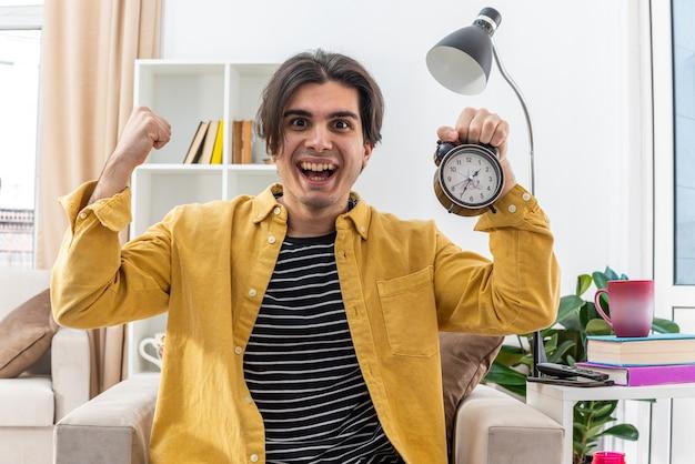 Jonge man in vrijetijdskleding met een wekker blij en opgewonden die vuist opheft als een wijnmaker die op de stoel zit in een lichte woonkamer