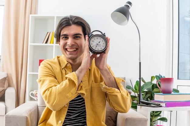 Jonge man in vrijetijdskleding met een wekker die blij en vrolijk glimlacht, breeduit zittend op de stoel in een lichte woonkamer