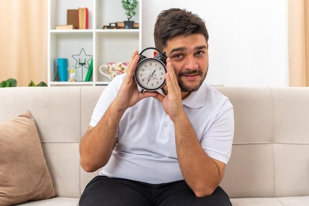 Jonge man in vrijetijdskleding met een wekker die met een glimlach op het gezicht kijkt, gelukkig en positief zittend op een bank in een lichte woonkamer