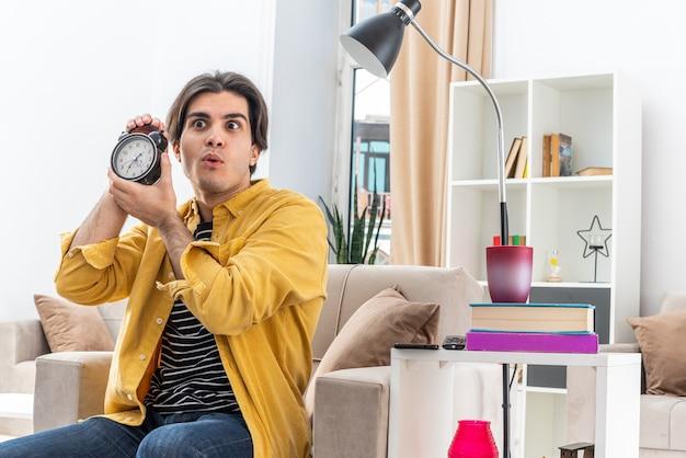 Jonge man in vrijetijdskleding met een wekker die verbaasd en verrast op de stoel zit in een lichte woonkamer