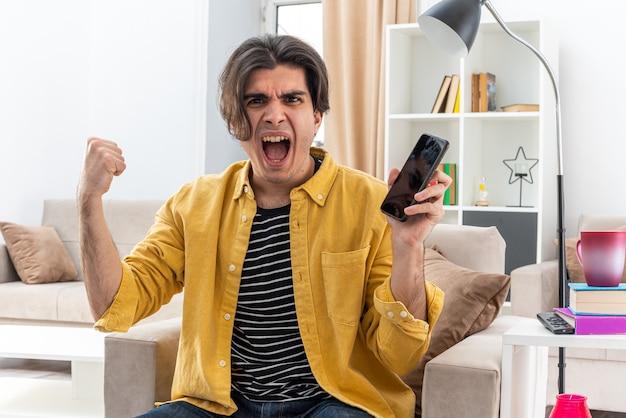 Jonge man in vrijetijdskleding met smartphone balde vuist gek gek schreeuwen gefrustreerd zittend op de stoel in lichte woonkamer