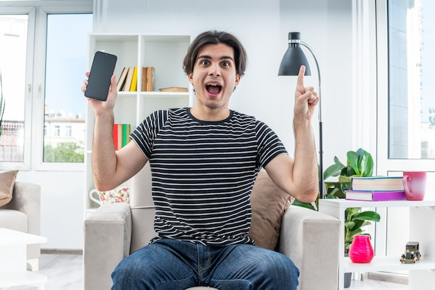 Jonge man in vrijetijdskleding met smartphone blij en verrast met wijsvinger met nieuw idee zittend op de stoel in lichte woonkamer