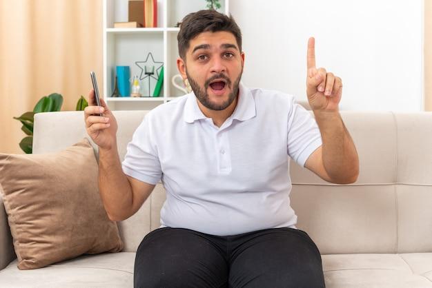 Jonge man in vrijetijdskleding met smartphone die er blij en verrast uitziet en laat zien dat wijsvinger een nieuw idee heeft zittend op een bank in een lichte woonkamer light