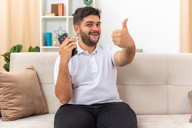 Jonge man in vrijetijdskleding met smartphone die er gelukkig en vrolijk uitziet en duimen opsteekt glimlachend breed zittend op een bank in lichte woonkamer living