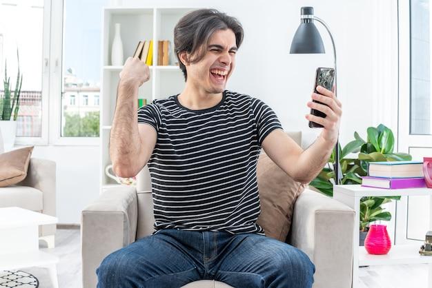 Jonge man in vrijetijdskleding met smartphone die ernaar kijkt, blij en opgewonden, vuist op de stoel zittend in een lichte woonkamer