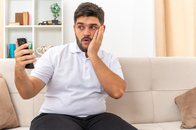 Jonge man in vrijetijdskleding met smartphone die naar het scherm kijkt verbaasd en verward zittend op een bank in een lichte woonkamer