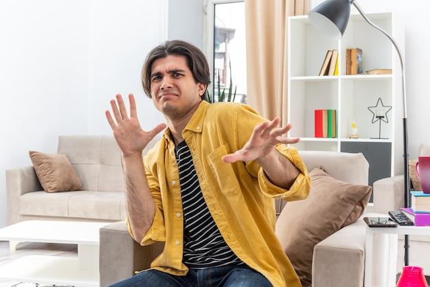 Jonge man in vrijetijdskleding met weerzinwekkende uitdrukking die een verdedigingsgebaar maakt met handen zittend op de stoel in lichte woonkamer living