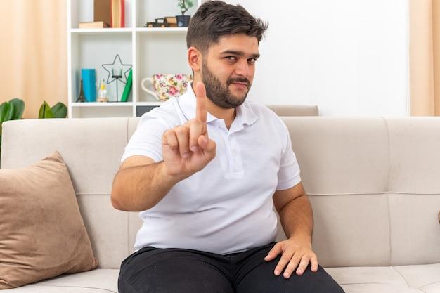 Jonge man in vrijetijdskleding met zelfverzekerde uitdrukking die een waarschuwingsgebaar van de wijsvinger laat zien, zittend op een bank in een lichte woonkamer