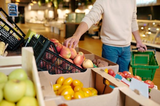 Jonge man in vrijetijdskleding neemt een appel uit een houten kist tijdens een bezoek aan een grote moderne supermarkt om eten te kopen