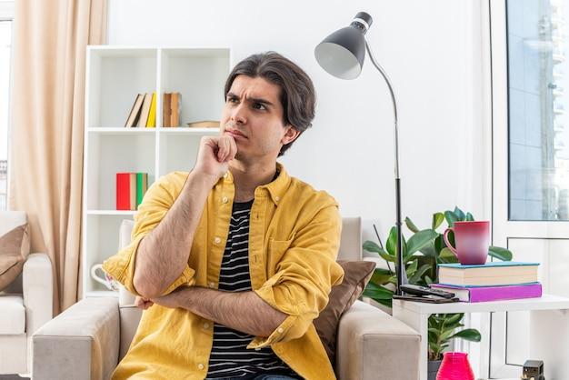 Jonge man in vrijetijdskleding opzij kijkend met peinzende uitdrukking met de hand op de kin denkend zittend op de stoel in een lichte woonkamer light
