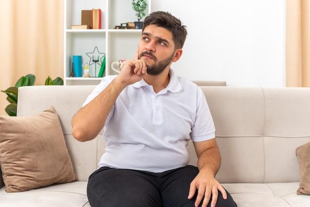 Jonge man in vrijetijdskleding opzij kijkend verbaasd zittend op een bank in lichte woonkamer