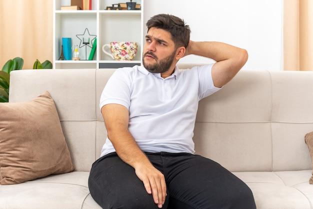 Jonge man in vrijetijdskleding opzij kijkend verward met hand op zijn hoofd zittend op een bank in lichte woonkamer