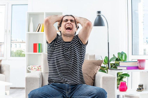 Jonge man in vrijetijdskleding schreeuwen gefrustreerd met handen op zijn hoofd zittend op de stoel in lichte woonkamer living